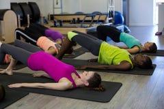 Donne che eseguono allungando esercizio sulla stuoia di esercizio Immagini Stock