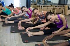 Donne che eseguono allungando esercizio sulla stuoia di esercizio nella palestra Immagine Stock