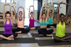 Donne che eseguono allungando esercizio sulla stuoia di esercizio nella palestra Immagini Stock Libere da Diritti