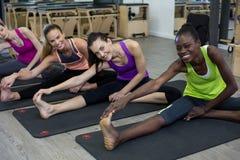 Donne che eseguono allungando esercizio sulla stuoia di esercizio nella palestra Fotografia Stock Libera da Diritti