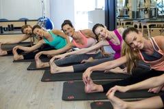 Donne che eseguono allungando esercizio sulla stuoia di esercizio nella palestra Fotografie Stock