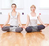 Donne che fanno esercitazione di yoga alla ginnastica Immagini Stock