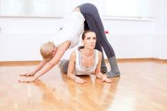 Donne che fanno esercitazione di yoga alla ginnastica Fotografia Stock