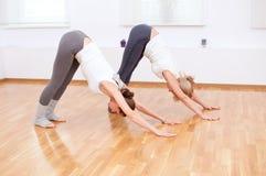 Donne che fanno esercitazione di yoga alla ginnastica Fotografie Stock
