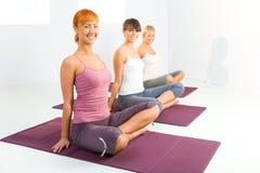 Donne che fanno i exercices di yoga Fotografia Stock