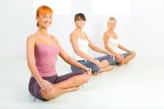 Donne che fanno i exercices di yoga Immagine Stock