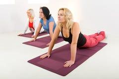 Donne che fanno i exercices sulla stuoia Fotografie Stock Libere da Diritti