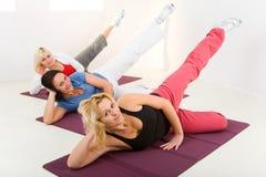 Donne che fanno i exercices sulla stuoia Immagini Stock