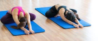 Donne che fanno indietro allungamento dell'yoga nella palestra di forma fisica Fotografie Stock