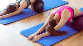 Donne che fanno indietro allungamento dell'yoga nella palestra di forma fisica Immagine Stock