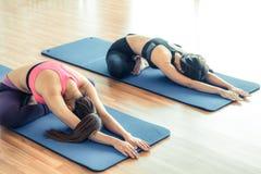 Donne che fanno indietro allungamento dell'yoga nella palestra di forma fisica Immagini Stock