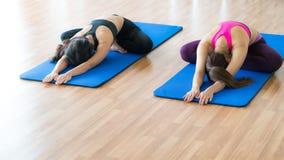 Donne che fanno indietro allungamento dell'yoga nella palestra di forma fisica Fotografia Stock
