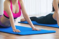 Donne che fanno indietro allungamento dell'yoga nella palestra di forma fisica Immagini Stock Libere da Diritti