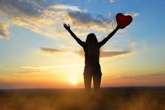 Donne che giudicano pallone nella forma del cuore disponibile al tramonto Immagine Stock