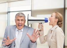 Donne che gridano all'uomo d'affari Stressed in ufficio immagine stock libera da diritti