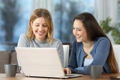 Donne che guardano il contenuto di media sulla linea in un computer portatile a casa Fotografia Stock Libera da Diritti