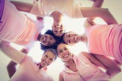 Donne che indossano rosa per cancro al seno con le armi intorno Immagine Stock
