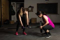 Donne che installano un bilanciere per il loro allenamento Fotografia Stock