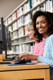 Donne che lavorano ai computer in biblioteca Fotografia Stock