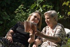 Donne che leggono all'esterno Fotografia Stock Libera da Diritti