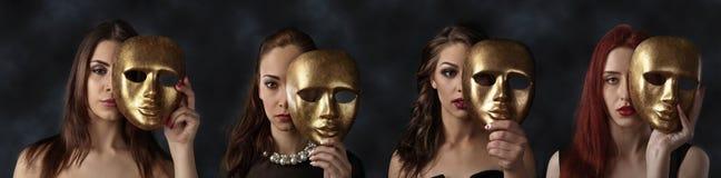 Donne che nascondono i fronti dietro le maschere dorate Fotografie Stock