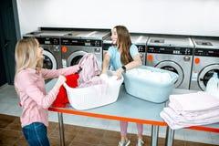 Donne che ordinano i vestiti nella lavanderia fotografia stock libera da diritti