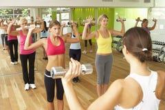 Donne che partecipano alla classe di forma fisica della palestra facendo uso dei pesi Fotografia Stock Libera da Diritti