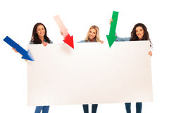 3 donne che presentano grande bordo indicando le frecce  Immagini Stock Libere da Diritti