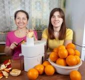 Donne che producono il succo di arancia fresco Immagine Stock