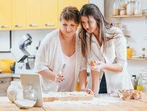 Donne che rendono a ricetta della compressa delle pasticcerie cottura online immagini stock libere da diritti
