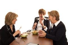 Donne che ridono durante il pranzo di lavoro Immagine Stock
