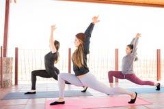 Donne che risolvono alla classe di yoga Fotografia Stock