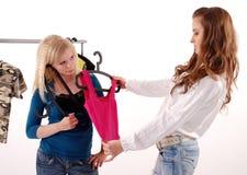 Donne che scelgono i vestiti in negozio Immagini Stock