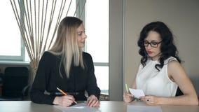 Donne che si siedono allo scrittorio, discutente gli scopi nell'ufficio stock footage