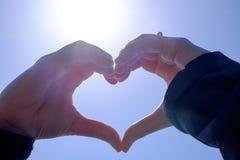 Donne che si tengono per mano in una forma del cuore Fotografia Stock