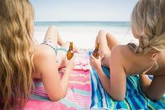 Donne che si trovano sulla spiaggia con la bottiglia di birra Immagini Stock