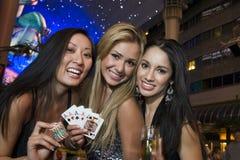Donne che tengono i chip, le carte da gioco e Champagne Glass del casinò Fotografie Stock