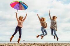 Donne che tengono ombrello divertendosi con gli amici Immagini Stock Libere da Diritti