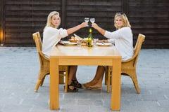 Donne che tostano i bicchieri di vino alla Tabella all'aperto Immagine Stock Libera da Diritti