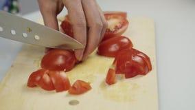 Donne che usando il pomodoro fresco del taglio dello scorrevole del coltello da cucina sul tagliere di legno Affettare pomodoro p archivi video