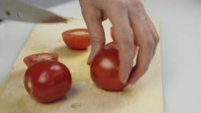 Donne che usando il pomodoro fresco del taglio dello scorrevole del coltello da cucina sul tagliere di legno Affettare pomodoro p video d archivio