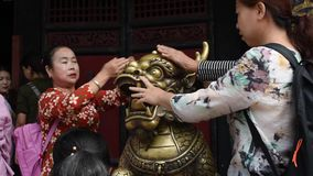 Donne cinesi che pregano in un tempio buddista stock footage