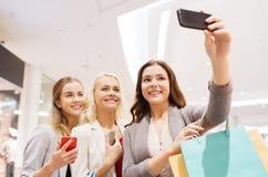 Donne con gli smartphones che comperano e che prendono selfie Fotografie Stock Libere da Diritti