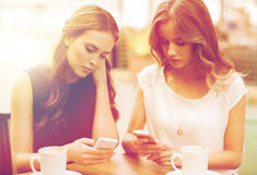 Donne con gli smartphones ed il caffè al caffè all'aperto Fotografia Stock