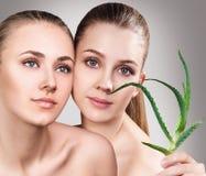 Donne con la pianta di vera dell'aloe e la pelle perfetta Fotografie Stock