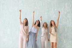Donne con le stelle filante, gruppo felice di amici che accendono le stelle filante Fotografia Stock
