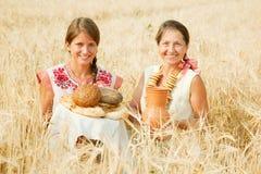 Donne con pane al giacimento dei cereali Immagine Stock