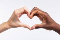 Donne con pelle bianca e nera che mostra cuore con le loro mani immagine stock libera da diritti