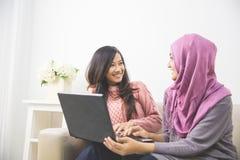 Donne con un computer portatile Immagine Stock