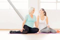 Donne contentissime allegre che si siedono su una stuoia di yoga Immagini Stock Libere da Diritti